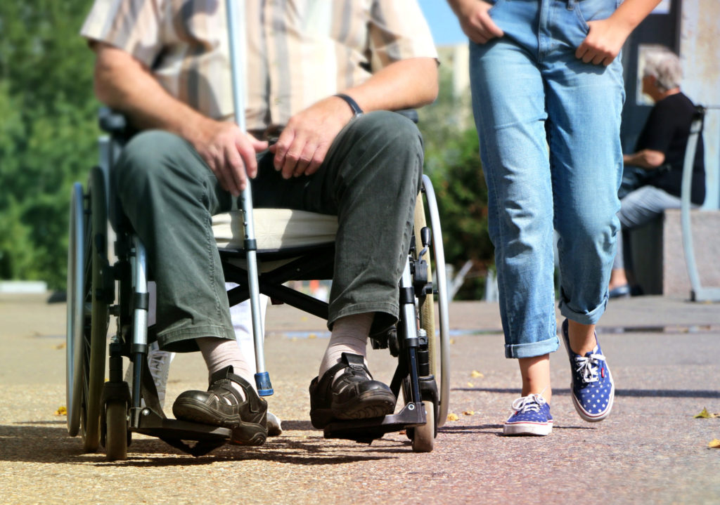 Jambes dune personne à pied et une autre en fauteuil roulant
